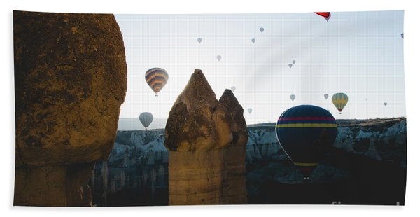 hot air balloons for tourists flying over rock formations at sunrise in the valley of Cappadocia. Beach Towel