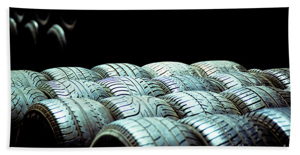 Old Tires And Racing Wheels Stacked In The Sun Beach Towel