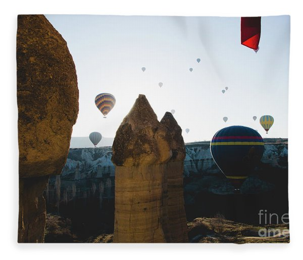 hot air balloons for tourists flying over rock formations at sunrise in the valley of Cappadocia. Fleece Blanket