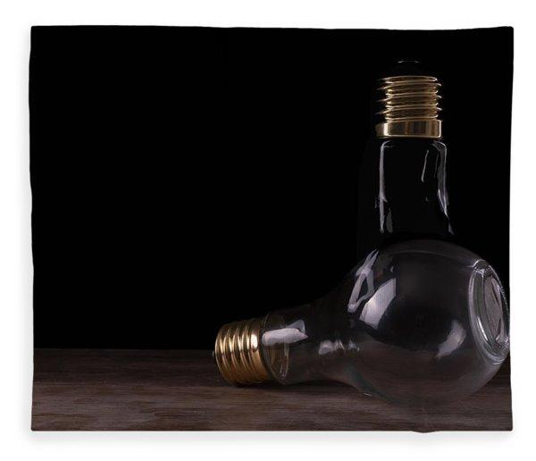 Two Light Bulbs Arranged On A Wooden Table  Fleece Blanket