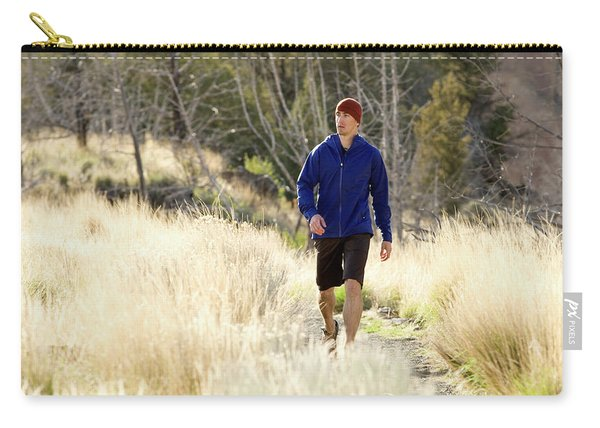 A Man In A Blue Jacket Walks Carry-all Pouch