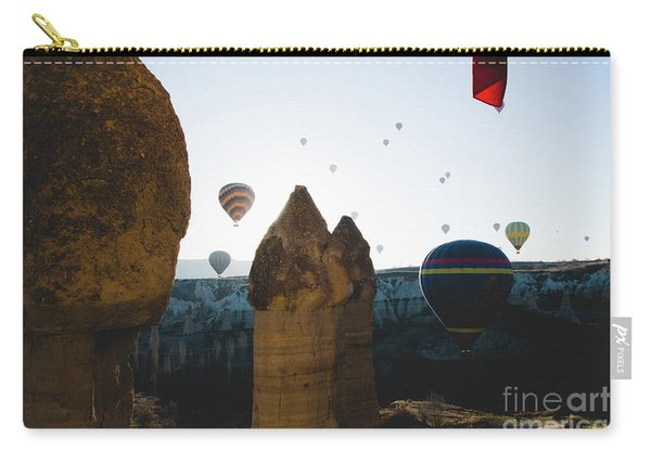 hot air balloons for tourists flying over rock formations at sunrise in the valley of Cappadocia. Carry-all Pouch