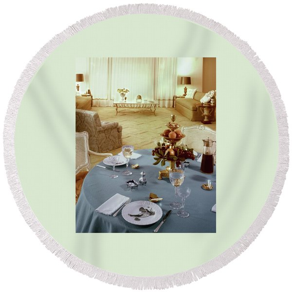 A Dining Room With A Blue Tablecloth And Ornate Round Beach Towel