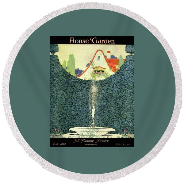 A Fountain With A Hedge In The Background Round Beach Towel