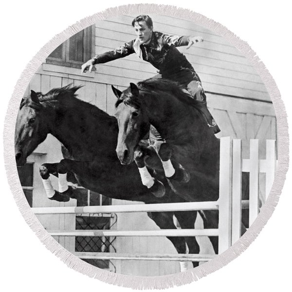 A Stunt Rider On Two Horses. Round Beach Towel
