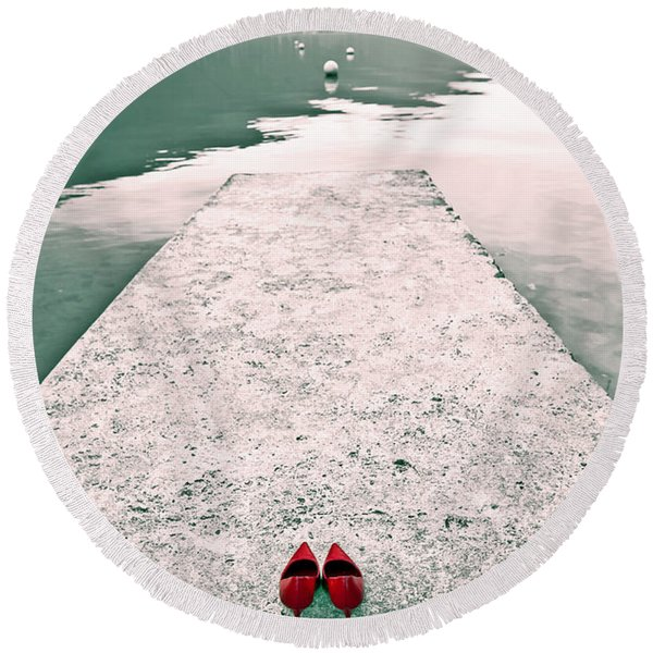 A Pair Of Red Women's Shoes Lying On A Walkway That Leads Into A Round Beach Towel