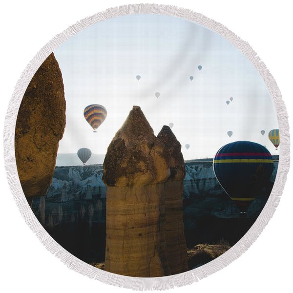 hot air balloons for tourists flying over rock formations at sunrise in the valley of Cappadocia. Round Beach Towel