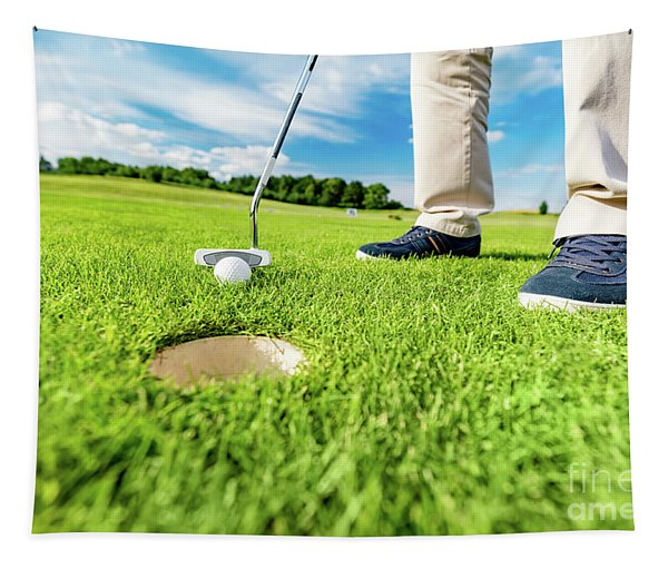 Golfer Putting Ball In The Hole On A Golf Course. Tapestry