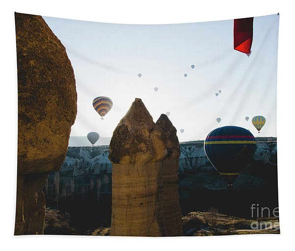 hot air balloons for tourists flying over rock formations at sunrise in the valley of Cappadocia. Tapestry