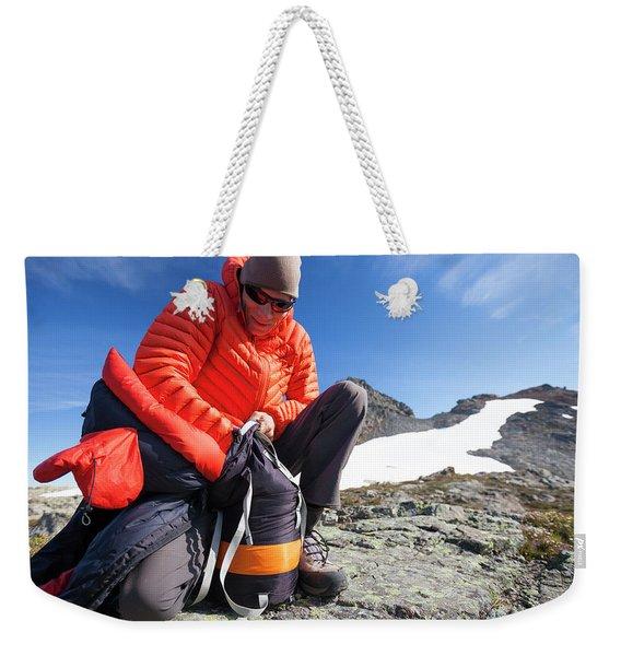 A Backpacker Stuffs His Sleeping Bag Weekender Tote Bag