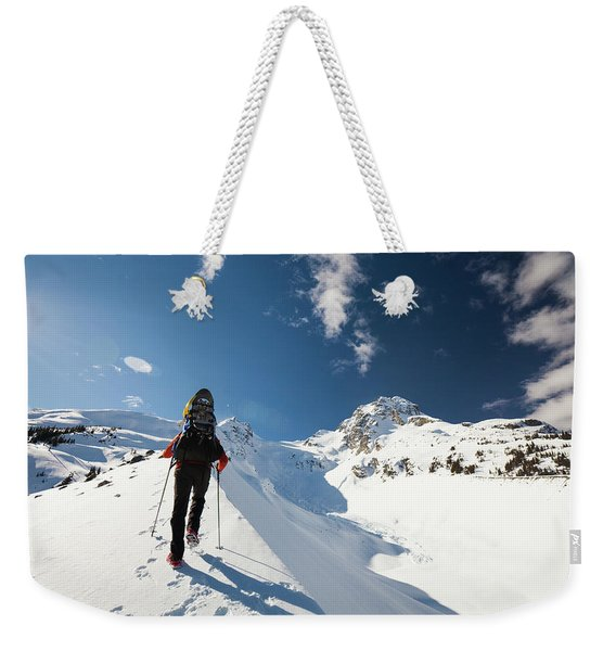 A Climber Walks Along The Snow Covered Weekender Tote Bag