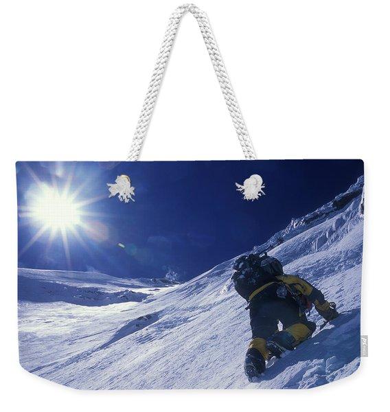 A Man Climbs A Steep Snow Covered Weekender Tote Bag