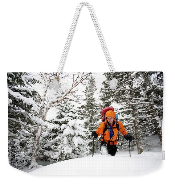 A Man Hiking Through The Snow On Mt Weekender Tote Bag