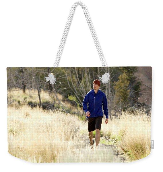 A Man In A Blue Jacket Walks Weekender Tote Bag