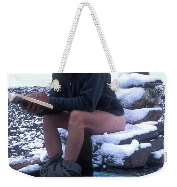 A Man Reads While Using A Snow-covered Weekender Tote Bag