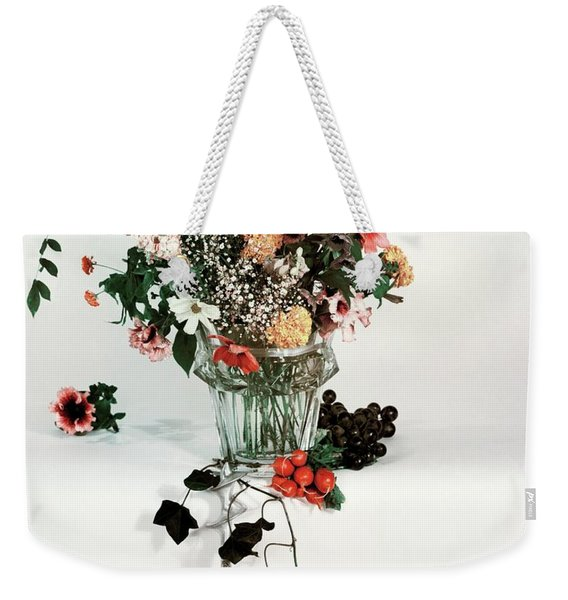A Studio Shot Of A Vase Of Flowers And A Garden Weekender Tote Bag