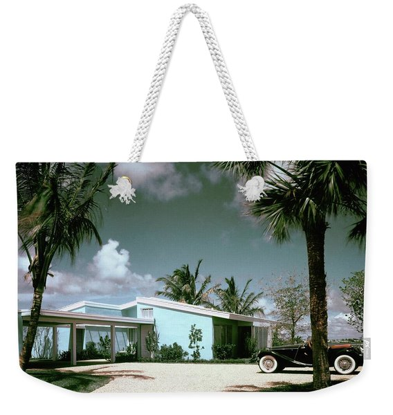 A Vintage Car Parked Outside A Blue House Weekender Tote Bag