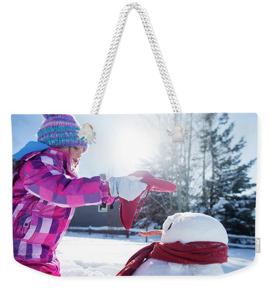 A Young Girl Building A Snowman Weekender Tote Bag