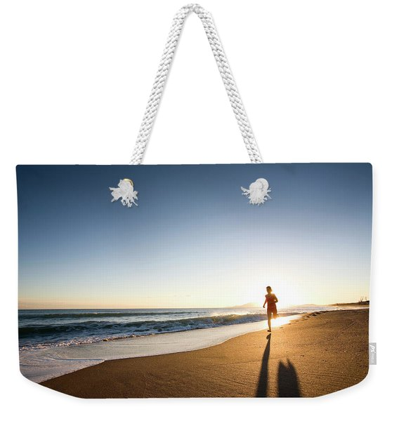 A Young Woman Running At Sunset Weekender Tote Bag