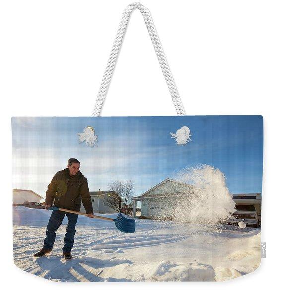 An Elderly Man Shovels Snow In Northern Weekender Tote Bag