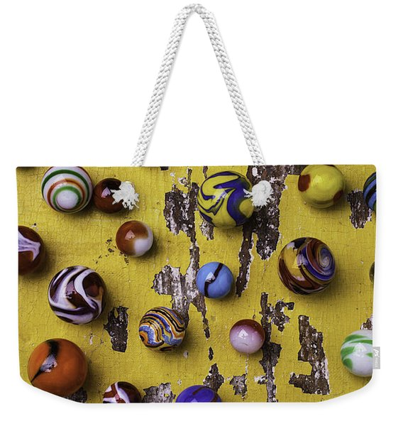 Marbles On Yellow Wooden Table Weekender Tote Bag