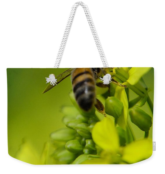 Weekender Tote Bag featuring the photograph Bee On A Yellow Background by Michael Goyberg