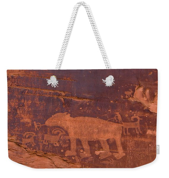 Weekender Tote Bag featuring the photograph Ancient Native American Petroglyphs On A Canyon Wall Near Moab. by Jim Thompson