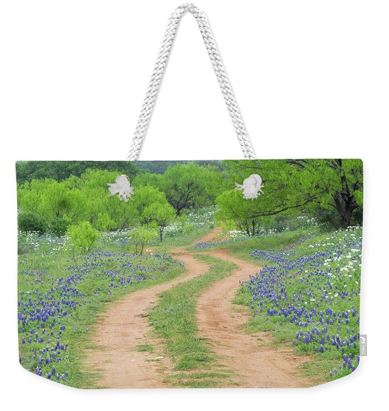 A Dirt Road Lined By Blue Bonnets Of Texas Weekender Tote Bag