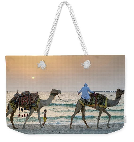 A Little Boy Stares In Amazement At A Camel Riding On Marina Beach In Dubai, United Arab Emirates Weekender Tote Bag