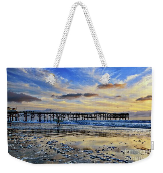 Weekender Tote Bag featuring the photograph A Surfer Heads Home Under A Cloudy Sunset At Crystal Pier by Sam Antonio Photography