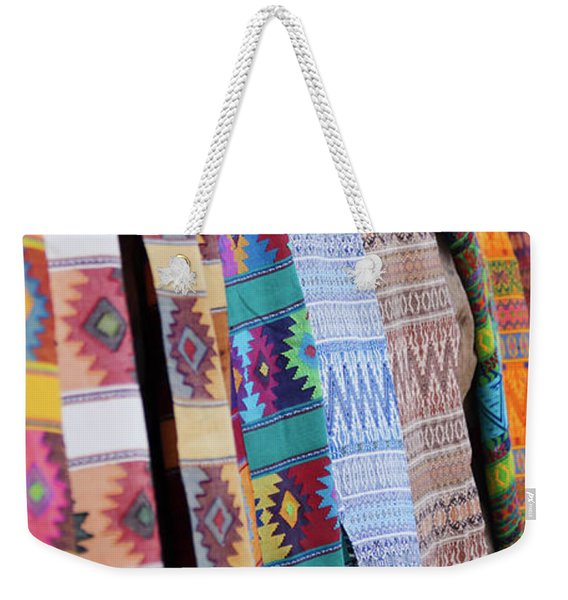An Assortment Of Colorful Blankets Hanging In A Row Weekender Tote Bag