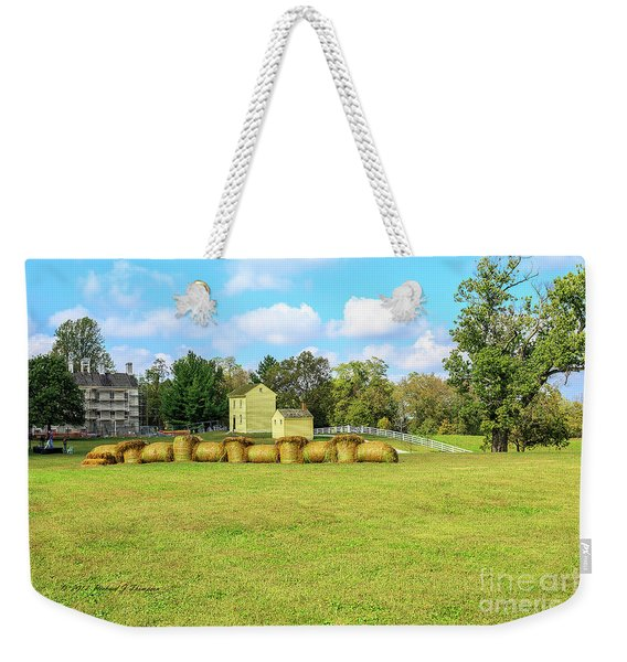 Weekender Tote Bag featuring the photograph Baled Hay In A Grassy Field by Richard J Thompson