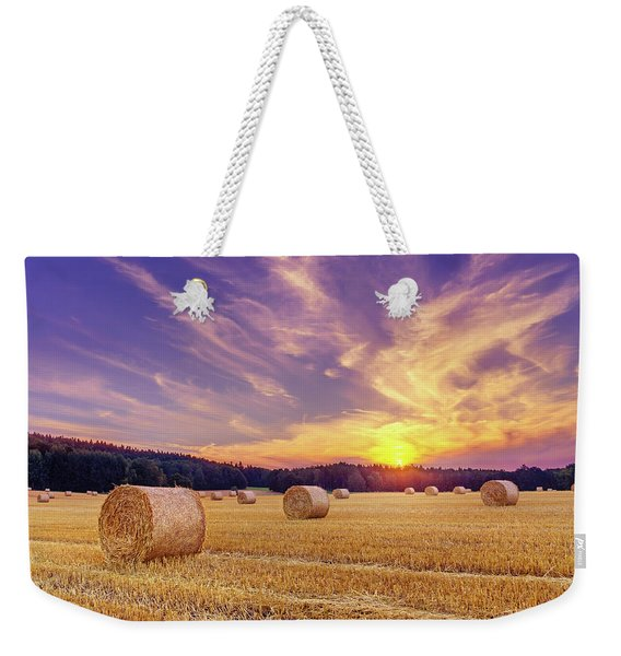 Weekender Tote Bag featuring the photograph Hay Bales And The Setting Sun by Dmytro Korol