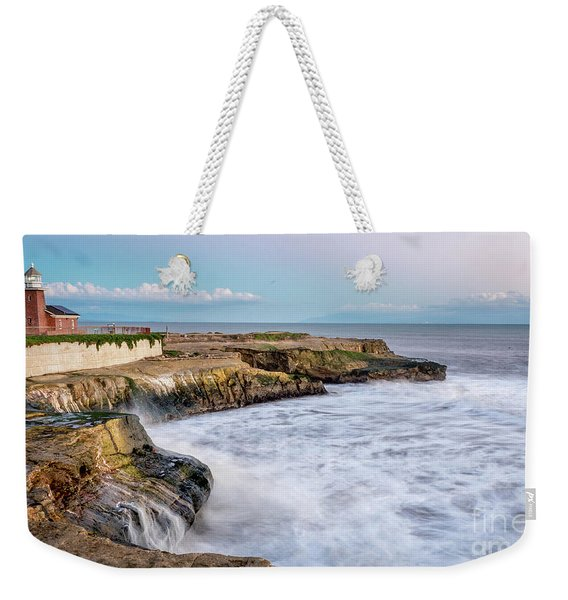 Long Exposure Of Waves Against The Cliff With Lighthouse In Shot Weekender Tote Bag