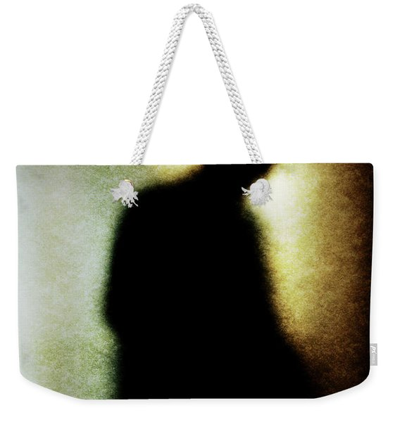 Weekender Tote Bag featuring the photograph Shadowy Man With Hat by Clayton Bastiani