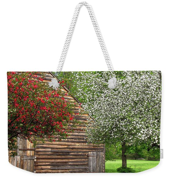 Weekender Tote Bag featuring the photograph Spring Flowers And The Barn by Nancy De Flon