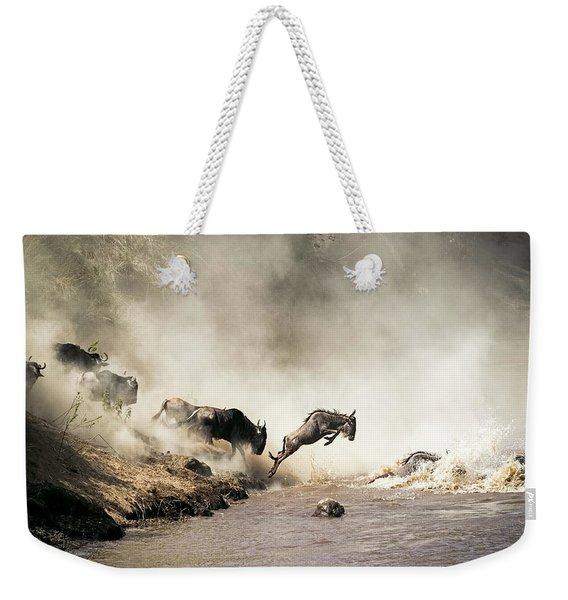 Wildebeest Leaping In Mid-air Over Mara River Weekender Tote Bag