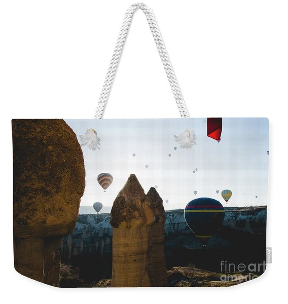 hot air balloons for tourists flying over rock formations at sunrise in the valley of Cappadocia. Weekender Tote Bag