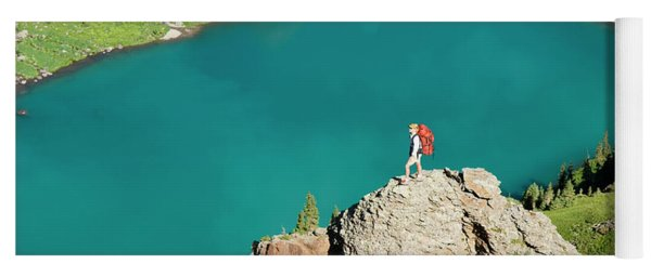 A Woman On A Rock Above Blue Lake Yoga Mat
