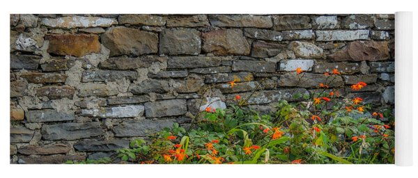 Orange Wildflowers Against Stone Wall Yoga Mat