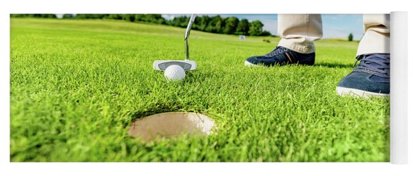 Golfer Putting Ball In The Hole On A Golf Course. Yoga Mat