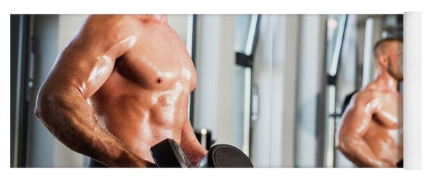 Muscular Man Working Out At A Gym. Yoga Mat