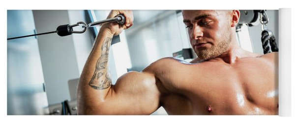 Muscular Man Working Out In A Gym. Yoga Mat