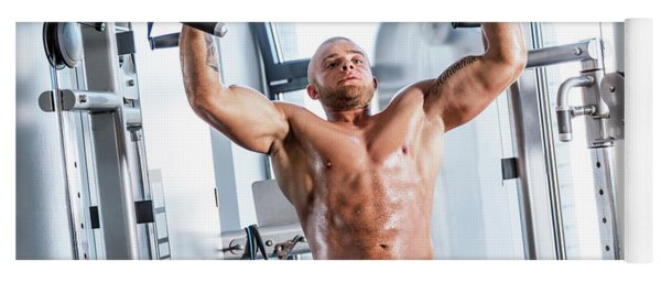 Muscular Strong Man Working Out At A Gym. Yoga Mat