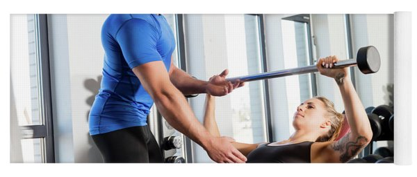 Personal Trainer Working With A Client At The Gym. Yoga Mat
