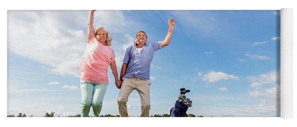 Senior Couple Jumping On A Golf Course. Yoga Mat
