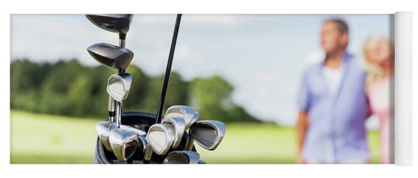 Set Of Golf Clubs With Senior Couple In The Background. Yoga Mat