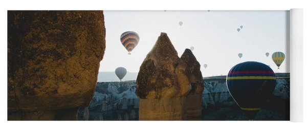 hot air balloons for tourists flying over rock formations at sunrise in the valley of Cappadocia. Yoga Mat