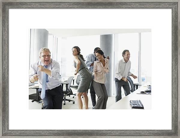 Businesspeople Dancing In Office Framed Print by Paul Bradbury
