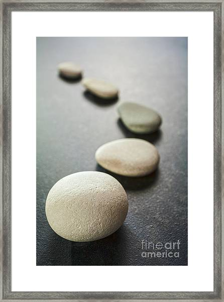 Curving Line Of Grey Pebbles On Dark Background Framed Print